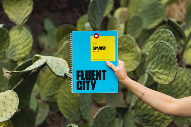 Get fluent in Spanish by immersing yourself in the language, a hand holding a book titled Fluent City