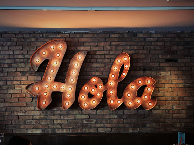 A neon sign over a brick wall saying Hola in Spanish