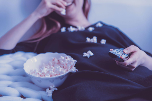 A woman binge watching foreign TV to learn multiple languages