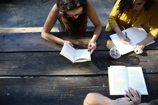 Students of multiple languages studying with textbooks