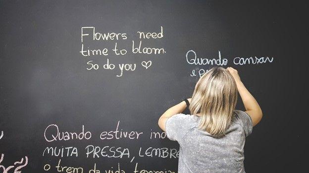 Teacher writing sentences in multiple languages on blackboard